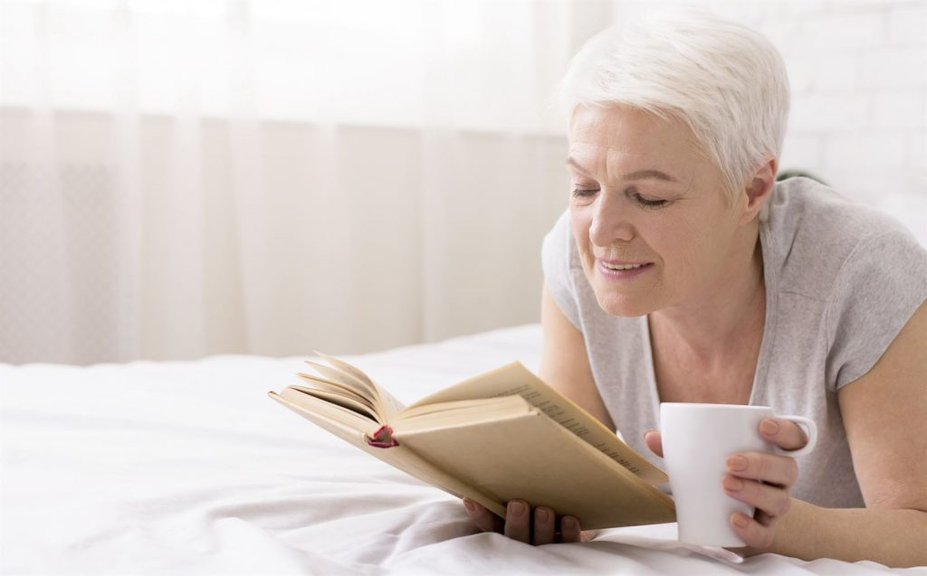 woman reading book on bed with tea